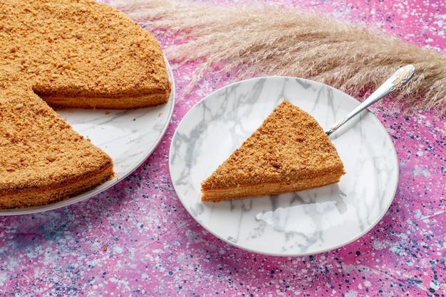 Вид спереди вкусный круглый торт внутри тарелки на ярко-розовом столе, пирог, бисквит, сладкая выпечка