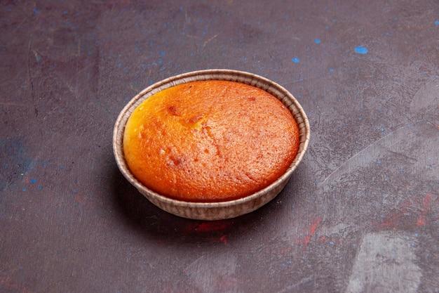 Vista frontale deliziosa torta rotonda dolce cuocere sullo sfondo scuro pasta per biscotti torta torta zucchero tè dolce