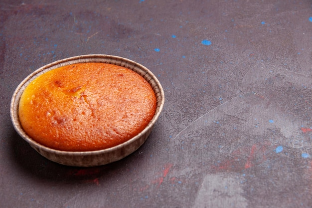 Vista frontale deliziosa torta rotonda dolce cuocere su sfondo scuro biscotto pasta dolce torta zucchero tè torta