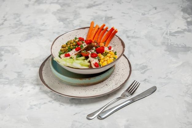 Vista frontale di una deliziosa insalata con vari ingredienti su un piatto su vassoi e posate su una superficie bianca con spazio libero