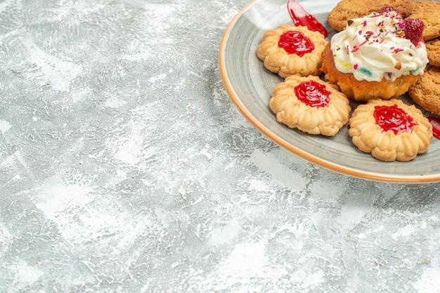 Vista frontale deliziosi biscotti di sabbia con biscotti e torta alla crema su spazio bianco