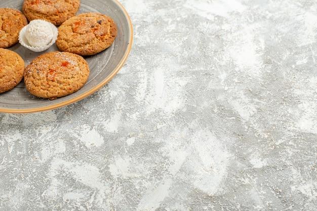 白いテーブルケーキクッキービスケットのプレート内のおいしい砂のクッキーの正面図