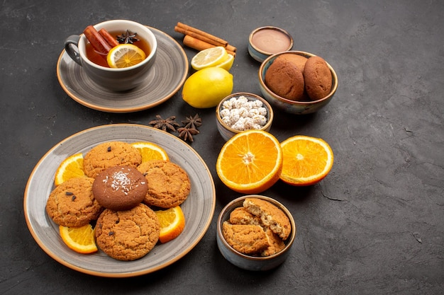 Front view delicious sand cookies with fresh oranges and cup of tea on dark background fruit biscuit sweet cookie citrus sugar