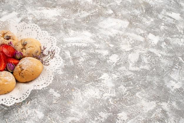 Vista frontale deliziosi biscotti di sabbia con fragole fresche su uno spazio bianco
