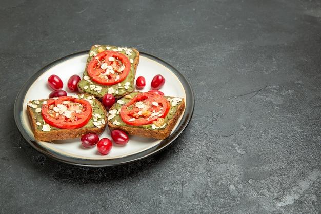 Вид спереди вкусные бутерброды с пастой из авокадо и помидорами внутри тарелки на сером фоне булочка с гамбургером закуска хлеб
