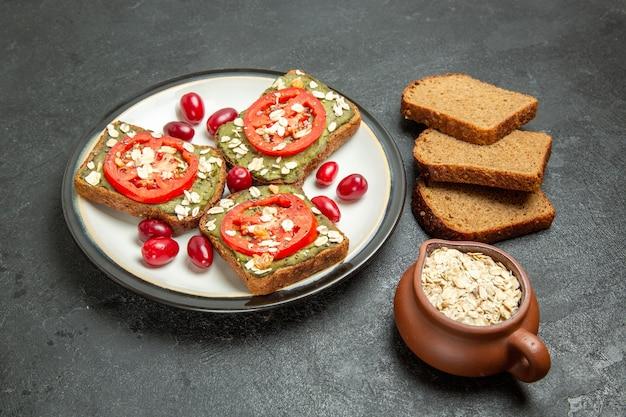 Вид спереди вкусные бутерброды с пастой авокадо и помидорами внутри тарелки на темно-сером фоне, булочка с гамбургером, закуска, хлеб