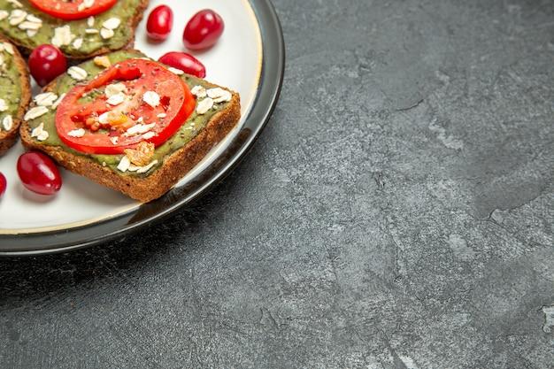 正面図灰色の机の上のプレートの中にアボカドパスタとトマトのおいしいサンドイッチハンバーガーサンドイッチパンスナックパン