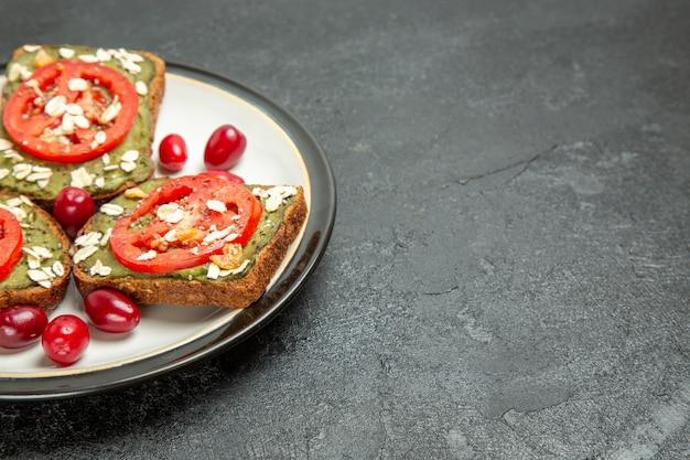 Vista frontale deliziosi panini con pasta di avocado e pomodori all'interno della piastra sullo sfondo grigio panino panino hamburger pane spuntino