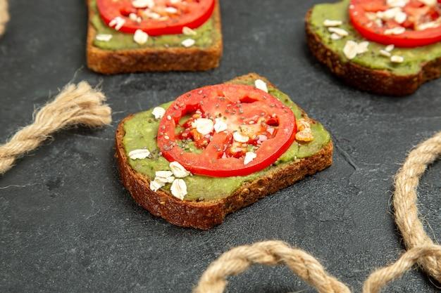 正面図灰色の背景にワサビと赤いトマトのおいしいサンドイッチパンハンバーガーサンドイッチミールスナック