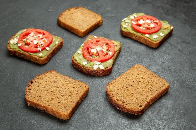 회색 배경 스낵 식사 햄버거 샌드위치 빵에 고추 냉이와 빨간 토마토와 전면보기 맛있는 샌드위치