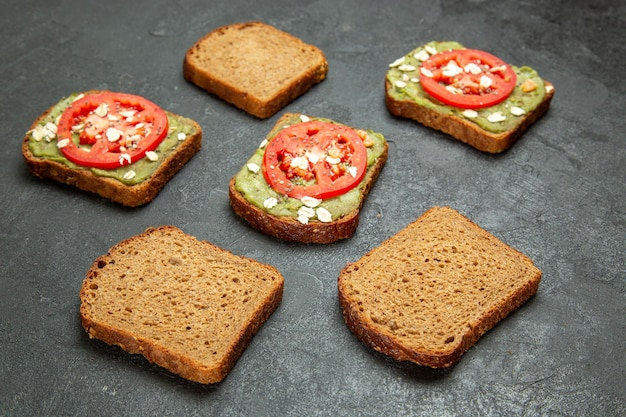 Front view delicious sandwiches with wassabi and red tomatoes on grey background snack meal burger sandwich bread