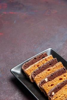 어두운 책상에 케이크 팬 안에 견과류와 함께 전면보기 맛있는 슬라이스 케이크 달콤한 차 케이크 설탕 쿠키 파이 비스킷