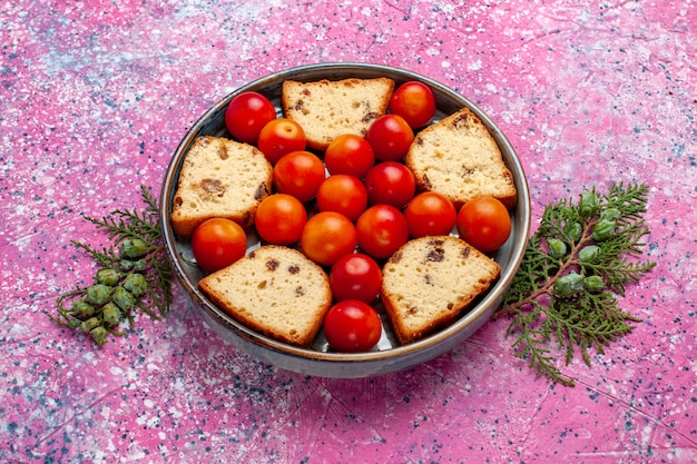 분홍색 표면에 팬 안에 신 신선한 자두와 전면보기 맛있는 슬라이스 케이크