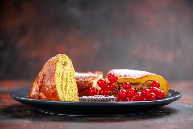 Вид спереди вкусный нарезанный пирог с красными ягодами на темном столе