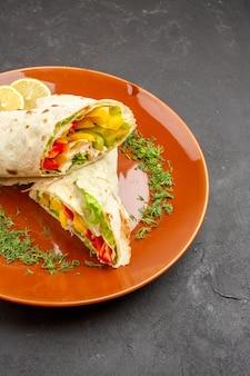 Vista frontale delizioso panino con insalata di shaurma affettato all'interno del piatto sullo spazio buio