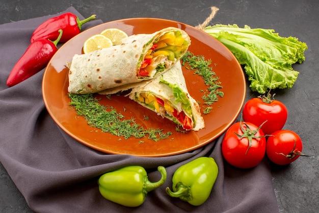 暗いスペースに新鮮な野菜を添えた、正面から見たおいしいスライス シャルマ サンドイッチ