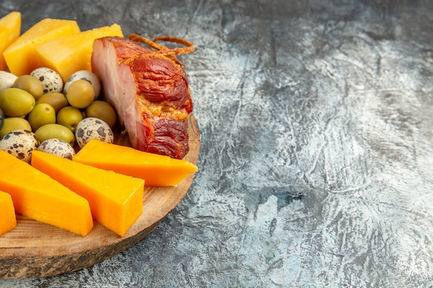 Front view of delicious snack including fruits and foods on a brown tray on ice background