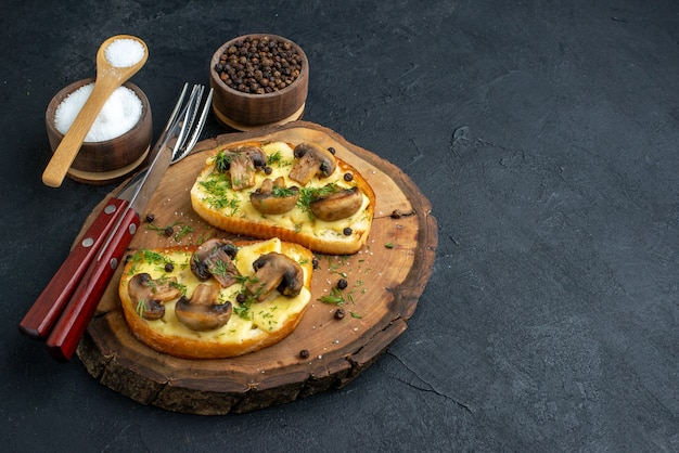 Front view of delicious snack with mushrooms cutlery set on wooden board and spices on black background