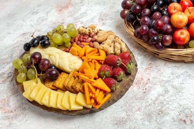 Vista frontale deliziosi spuntini cips uva formaggio e noci su uno spazio bianco