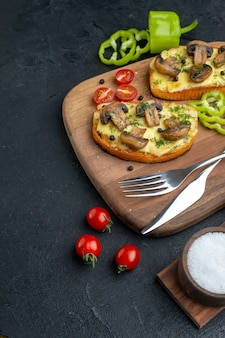 Front view of delicious snacks with mushroom fresh vegetables and cutlery set on wooden cutting board spices on the left side on black background