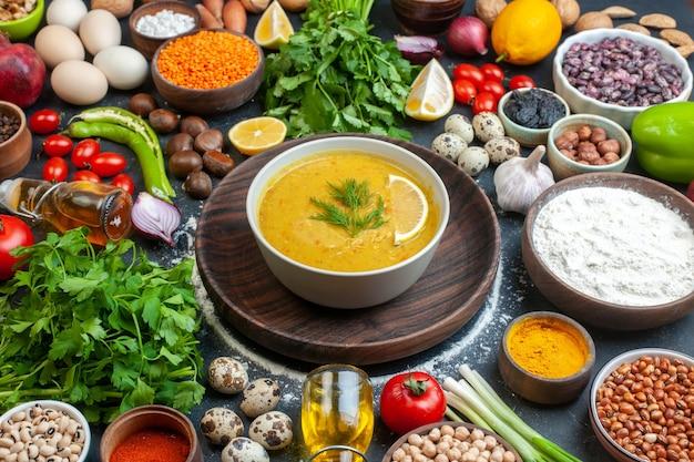 Vista frontale di una deliziosa zuppa servita con limone e verde in una ciotola bianca su vassoio di legno verdure alimenti bottiglia di olio spezie su tavola nera