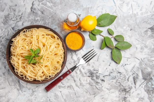 Vista frontale deliziosi spaghetti su tavola bianca pasta pasta limone