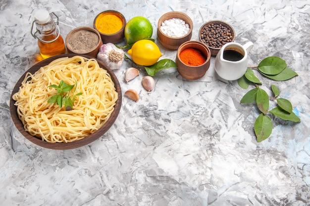 Vista frontale deliziosi spaghetti con condimenti su pasta bianca leggera da tavola