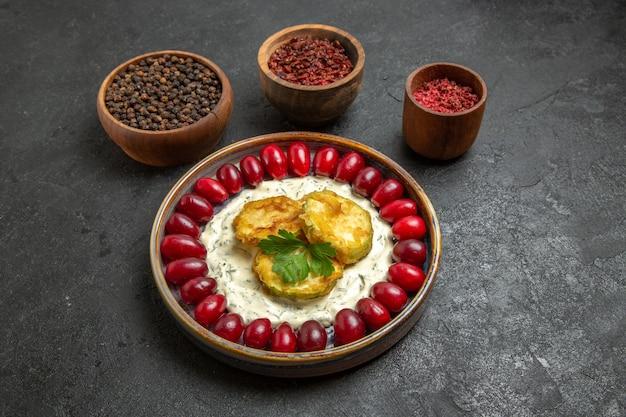 灰色の空間に新鮮な赤いハナミズキと調味料を使った正面図のおいしいカボチャ料理