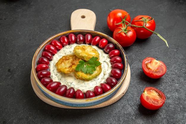 ダークグレーの空間に新鮮な赤いハナミズキとトマトを添えた正面図のおいしいカボチャ料理