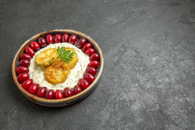 Vista frontale delizioso pasto di zucca con cornioli rossi freschi su uno spazio grigio