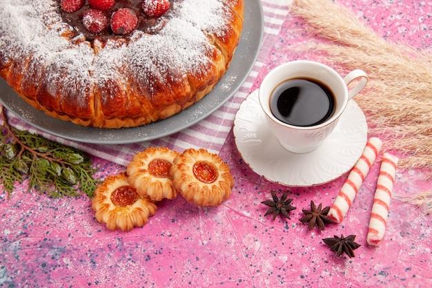 Vista frontale deliziosa torta di fragole zucchero in polvere con una tazza di tè e biscotti sulla superficie rosa chiaro torta biscotti dolci tè
