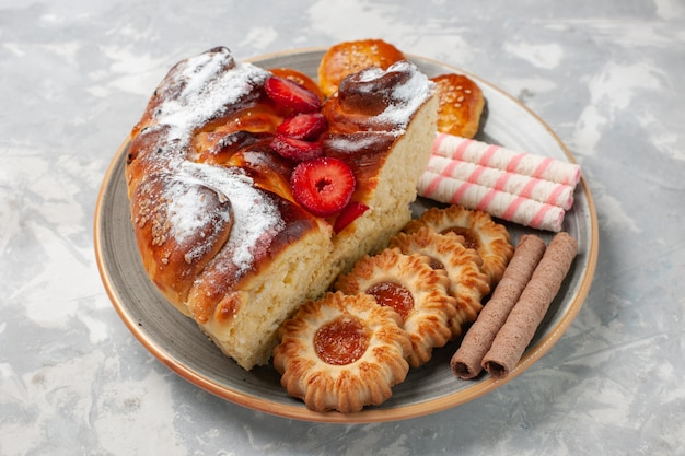 正面図クッキーと白い机の上の小さなケーキとおいしいストロベリーケーキ