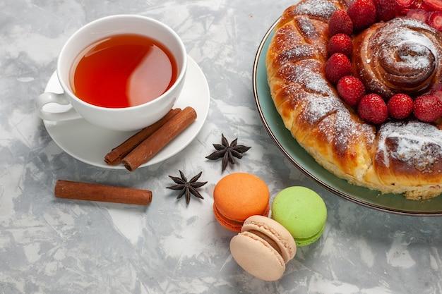 Torta di fragole deliziosa vista frontale con macarons e tazza di tè sulla scrivania bianca