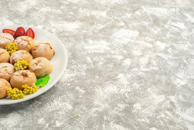 正面図白い背景の上のプレート内のおいしいシュガークッキーシュガークッキー甘いビスケットケーキティー