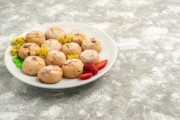 Вид спереди вкусное сахарное печенье внутри тарелки на белом полу сахарное печенье сладкий бисквитный торт чай