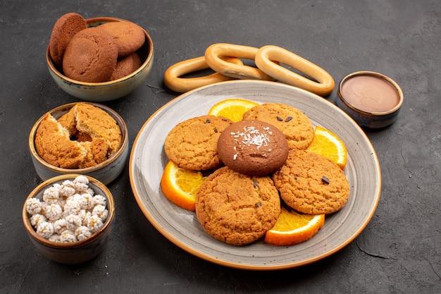 Vista frontale deliziosi biscotti di zucchero con arance fresche a fette su sfondo scuro biscotto biscotto torta di zucchero dolce da dessert