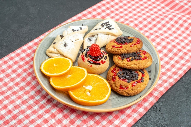 Front view delicious sugar cookies with pastries and orange on dark surface cake sugar biscuit sweet cookies tea