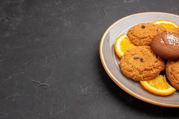 暗い背景のプレートの内側にスライスしたオレンジが付いたおいしいシュガークッキーの正面図シュガービスケットの甘いクッキーフルーツ