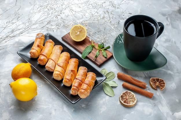 正面の白いテーブルにレモンシナモンと紅茶のおいしい甘い腕輪、ペストリーケーキ甘い砂糖を焼く