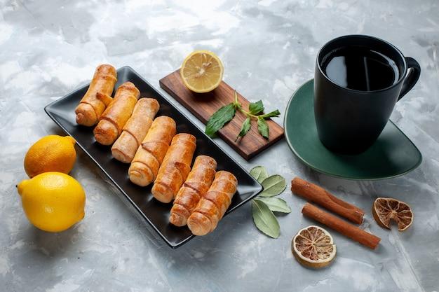 Vista frontale deliziosi braccialetti dolci con limone cannella e tè sul tavolo luminoso, torta di pasticceria cuocere zucchero dolce