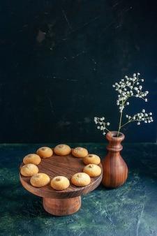 Vista frontale deliziosi biscotti dolci su biscotto blu scuro torta di zucchero torta tè foto dessert