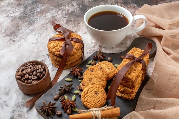 軽いココアシュガーティークッキーの甘いケーキの色にコーヒーの種と一杯のコーヒーが入ったおいしい甘いビスケットの正面図