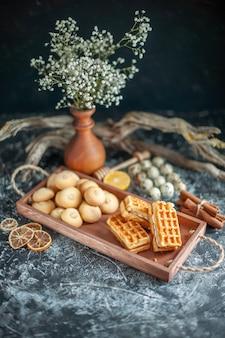 Vista frontale deliziosi biscotti dolci con piccole torte su torta di noci di biscotto di zucchero a torta dolce di colore grigio chiaro