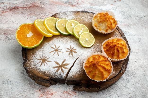 Vista frontale deliziose torte dolci con fette di limone sulla superficie bianca biscotto dolce cuocere il biscotto torta di zucchero torta