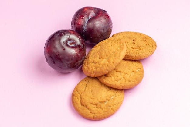 Вид спереди вкусное сладкое печенье, запеченное со сливами на розовом фоне, печенье сладкое сахарное печенье, чай