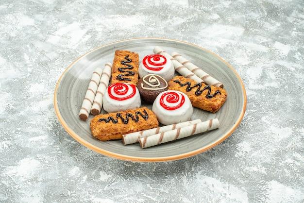 Vista frontale deliziosi biscotti dolci e torte su uno spazio bianco
