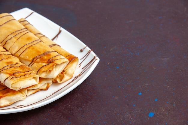 Вид спереди вкусной сладкой выпечки внутри тарелки на темном пространстве