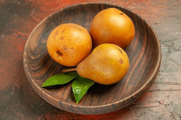 暗い背景の木の果樹リンゴの写真のプレート内のおいしい甘い梨の正面図