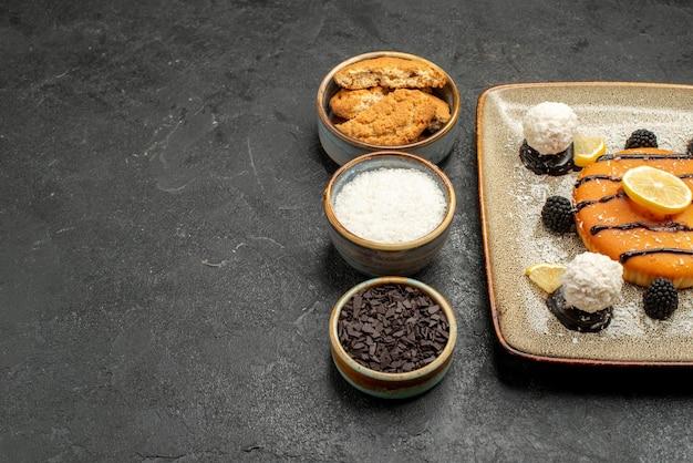 Vista frontale deliziosa torta dolce con caramelle al cocco su torta grigia torta biscotto dolce biscotto