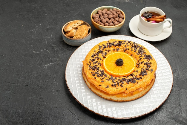 Front view delicious sweet pie with cup of tea on dark background cookie biscuit dessert tea cake pie